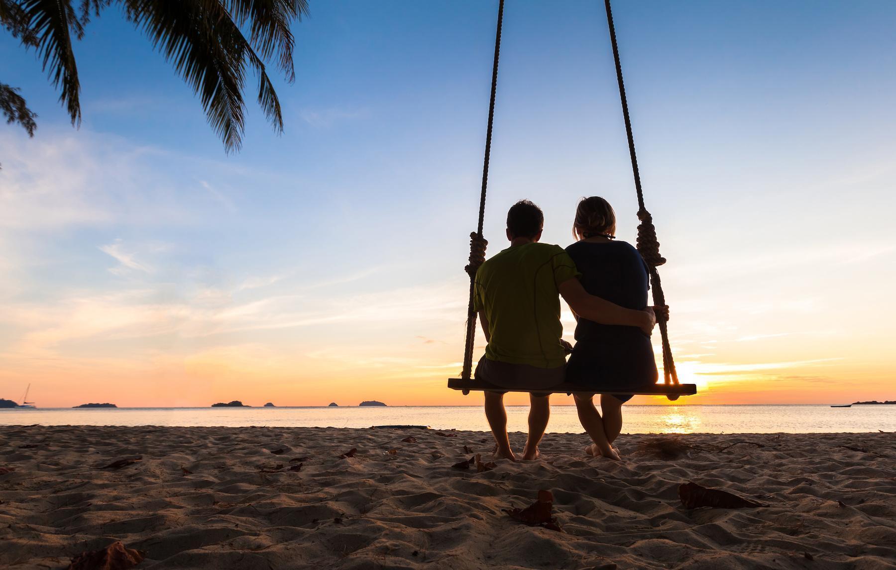Couple on paradise beach resort sharing honeymoon